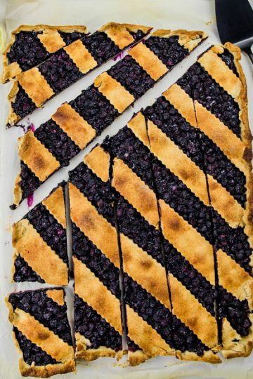 Blueberry Slab Pie is fresh blueberries, cinnamon and lemon juice baking into a buttery and crisp shortbread crust. Easily cuts into bars and feeds a crowd!