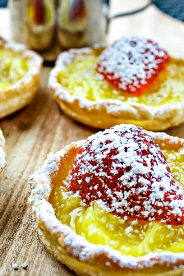 Cool, tangy and dotted with fresh strawberry this simple mini lemon tart dessert takes only 4 easy ingredients and no special pans to make them! #mustlovehomecooking
