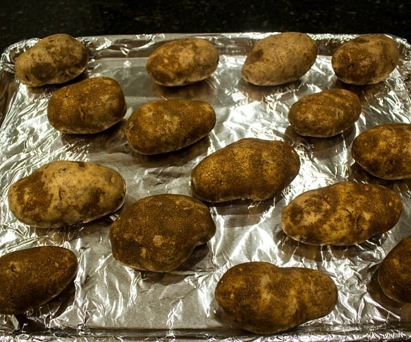 russet potatoes on foil lined baking sheet ready for the oven