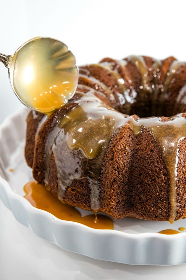 pouring toffee glaze over baked pumpkin cake
