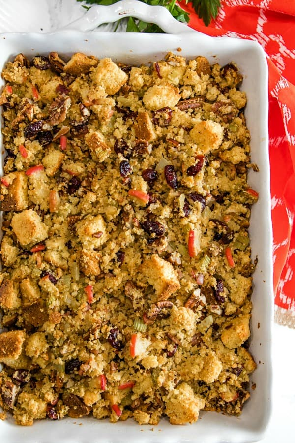 Pecan Apple Cornbread Stuffing made with toasted cornbread , crisp apples, pecans and cranberries, is a delicious sweet and savory dressing that'll be a hit on your holiday table. #mustlovehomecooking