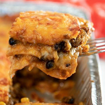 Easy Mexican Beef Lasagna - it's a Taco Tuesday favorite with layers of seasoned ground beef, tortillas, black beans, salsa and mounds of melted cheese. A freezer meal that's ready to just pop in the oven! #mustlovehomecooking