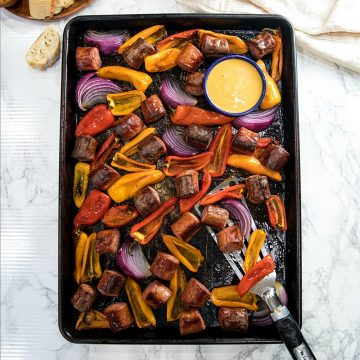 Delicious, versatile and fast, this Sheet Pan Smoked Sausage and Mini Peppers tossed with olive oil is an entire meal ready in 30 minutes!