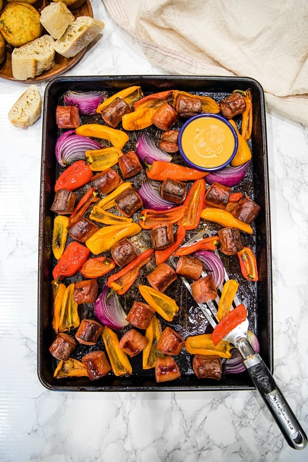 Delicious, versatile and fast, this Sheet Pan Smoked Sausage and Mini Peppers tossed with olive oil is an entire meal ready in 30 minutes! #mustlovehomecooking