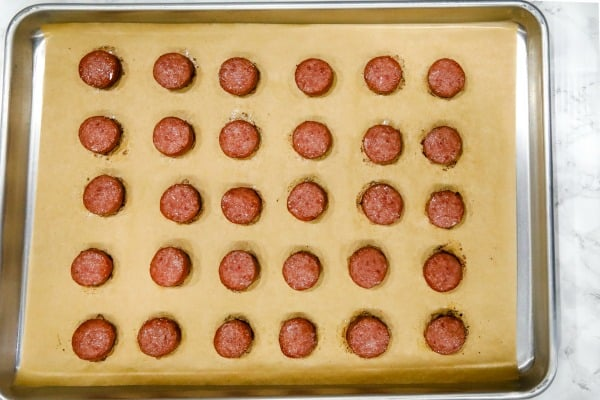 baked smoked sausage on parchment sheet on sheet pan