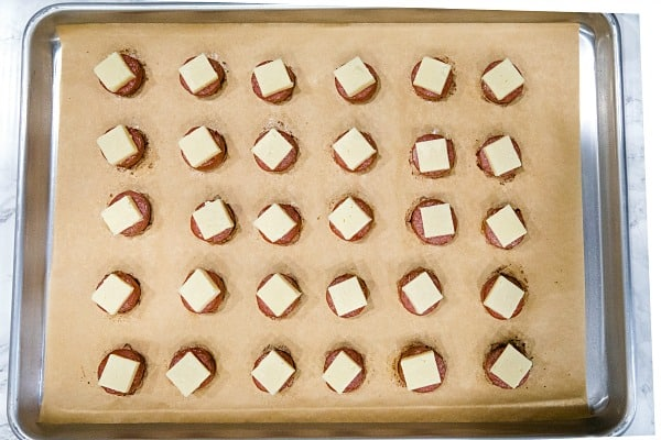 baked smoked sausage with cheese cube on parchment sheet on sheet pan