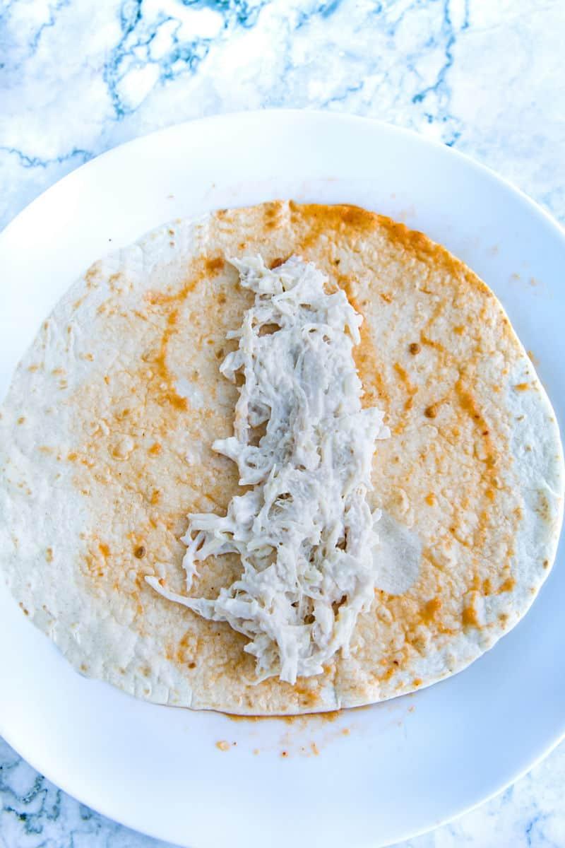 Enchalada chicken filling on flour tortilla