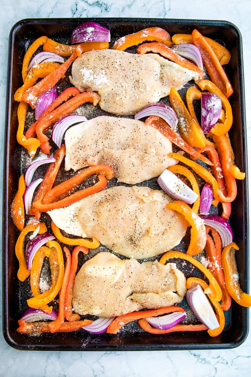Chicken and vegetables ready for the oven on large sheet pan
