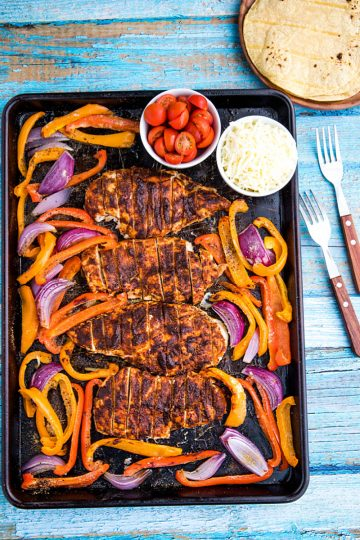 Classic chicken fajitas, with a twist, made easy on one sheet pan! An easy and delicious dinnertime favorite of juicy, adobo brushed chicken breasts, fresh bell pepper and onions all wrapped up in a soft flour tortilla. #mustlovehomecooking #mexicandinner #sheetpanrecipe