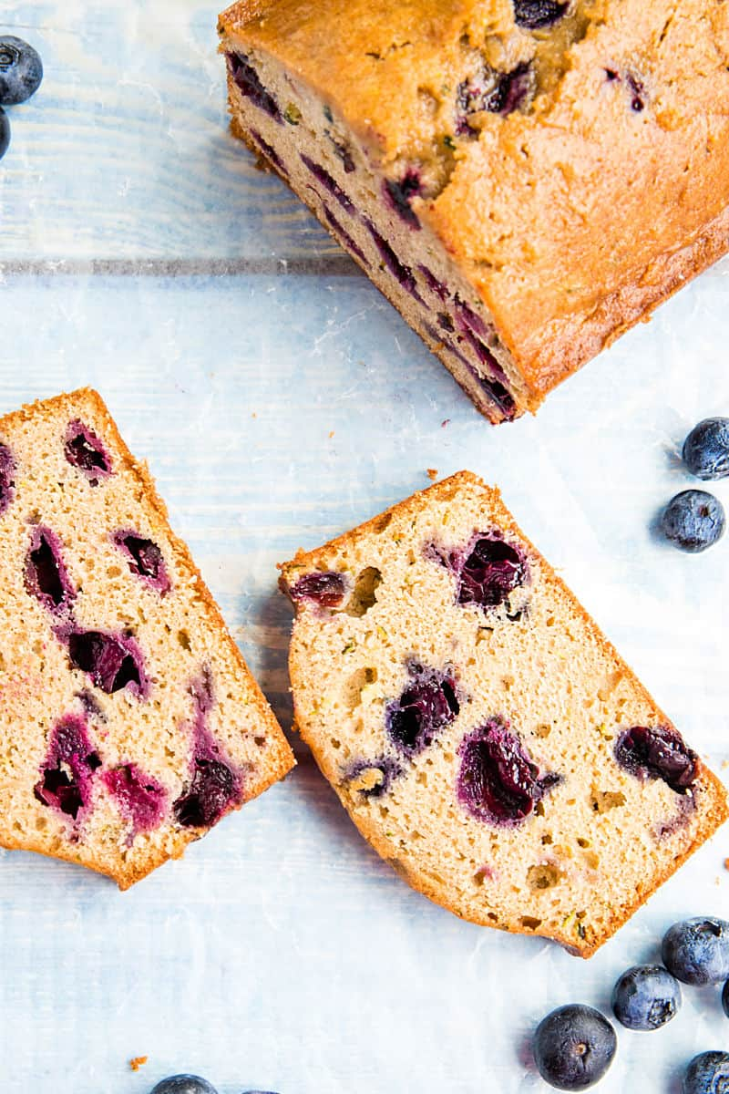 Blueberry Zucchini Bread is super simple and easy to make from scratch! This moist quick bread is made healthy with bursting blueberries, fresh zucchini and applesauce. #mustlovehomecooking