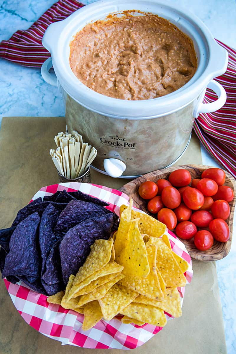 Creamy hot bean dip is loaded with refried beans, melted cheese, silky sour cream, and zesty spices. It's made in the slow cooker for easy, stay-warm serving or the oven for luscious cheese on top! #mustlovehomecooking