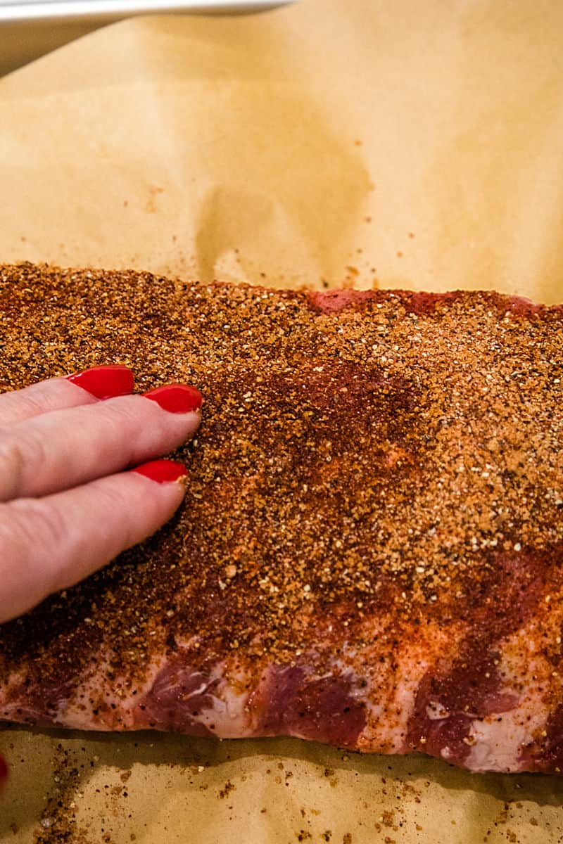 Rubbing spice mixture into rib meat.
